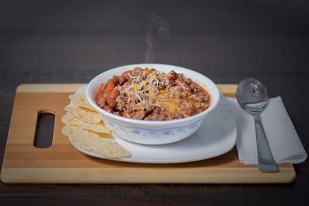 신장 콩 쇠고기 호박 피망 달콤한 옥수수 토마토 양파 마늘 토틸라 칩으로 만든 칠리 요리의 화이트 그릇.