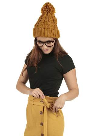 Sexy smiling geek woman wearing a plain black tee and mustard yellow bobble hat