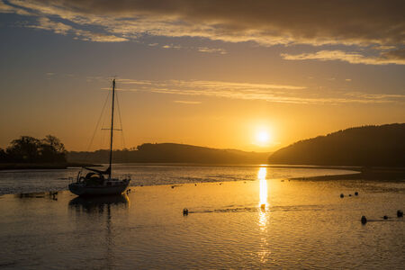 Sunrise on the river lynher with beautiful sky and golden reflections at st germans, cornwall, uk Banco de Imagens