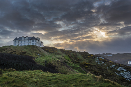 Liskeard, United Kingdom, 12 April 2015. A photo taken at sunrise of the Mullion Cove Hotel at Mullion, Cornwall, UK, a beautiful Cornish holiday destination visited by people the world over. Banco de Imagens - 58505496