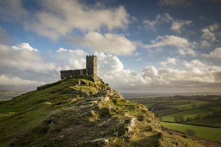 Brentor Church with stormy cloudy sky in the autumn afternoon sunshine, Devon, UK Banco de Imagens