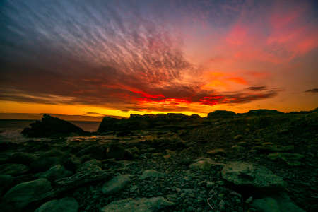 Dramatic night sky on fire off the rocky coastal landscape at Cape Palliser at sunset Stockfoto