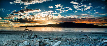 Dramatic cloudscape and Sunset flare over silhouetted Kapiti island at Paraparaumu beach covered in driftwood and beach art Stock Photo