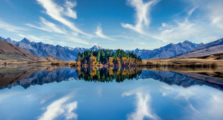 Stunning mountain reflections on the still water in a high country lake in New Zealand
