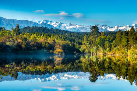 Mirror image reflections of the snow capped Southern Alps on Okarito Lagoon on the West Coast Archivio Fotografico