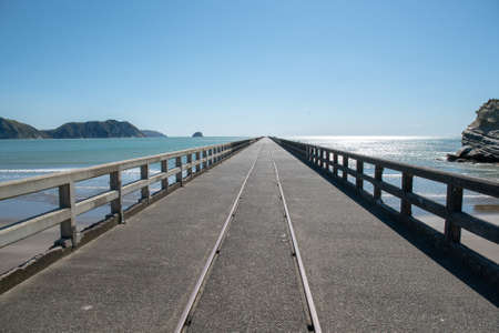 Railway track down the middle of the very long historic wharf at Tolaga Bay