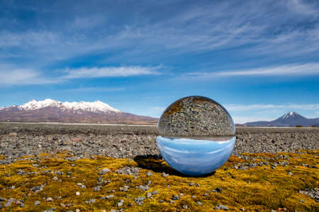 The Central Plateau snow capped volcanoes in the Desert road reflected in a crystal ball sitting on some yellow moss at the side of State Highway one