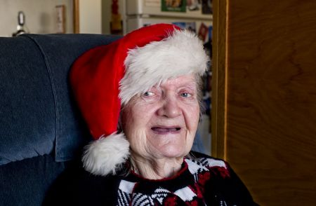 sequester: An Elderly women in the Christmas spirit with a Santa hat.  Stock Photo