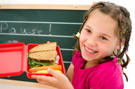laughing girl opens a healthy lunchbox in front of a blackboard