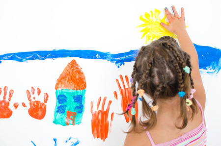Girl paints with finger paints a picture of a house
