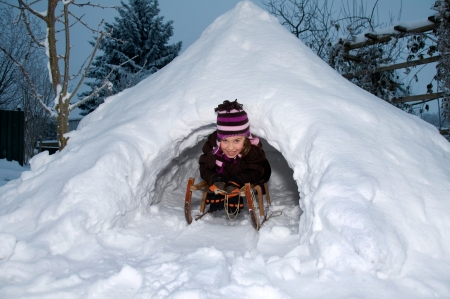 Girl on the sled in self-built igloo imd the wintry dusk  photo