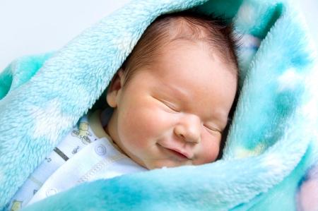 Neugeborenes Baby in einem warmen Babydecke liegend und lächelt Standard-Bild - 25268413