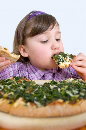 hungry children: Little girl devours Pizza Stock Photo