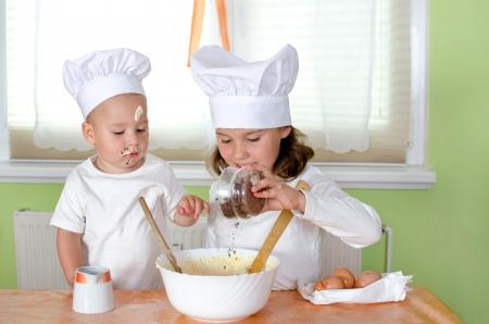 Siblings bake cakes in chef uniform Banco de Imagens