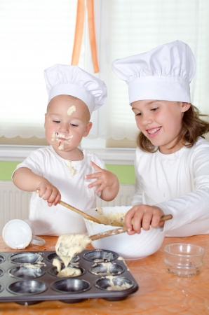 mother'sday: Kids at chef uniform baking Mufins for Mothersday Stock Photo
