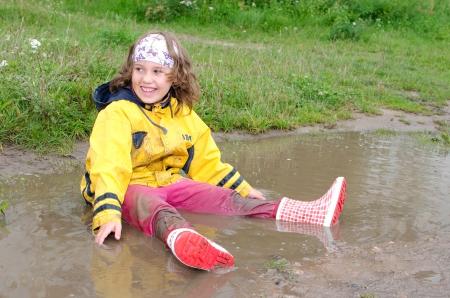 Het meisje zit met rubberen laarzen in een plas, Stockfoto