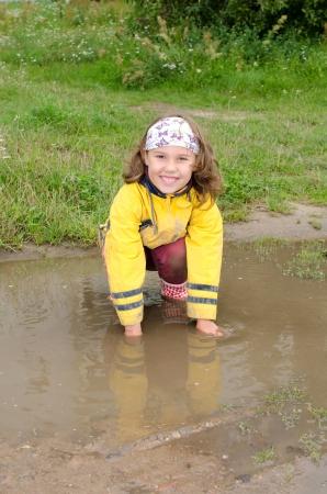 Meisje zitten in de regen plas en lacht in de camera;
