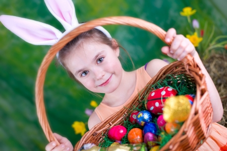 chocolate eggs: Laughing girl with Easter basket and bunny ears in front of a green background Stock Photo