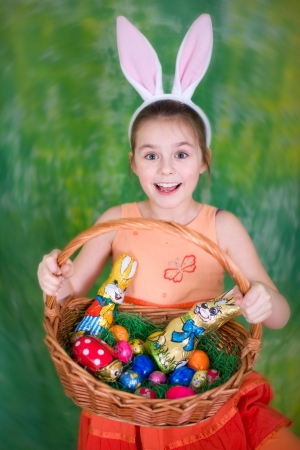 easter sunday: Laughing girl with Easter basket and bunny ears in front of a green background Stock Photo