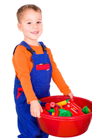 optional: Little boy in blue men cleans up his toys, optional Stock Photo
