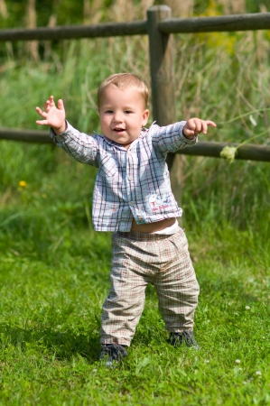 strive for: Baby s first steps on a green meadow Stock Photo