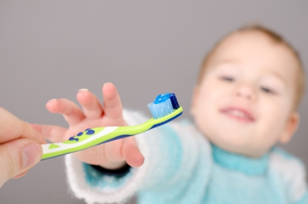 Little boy reaching for kids toothbrush