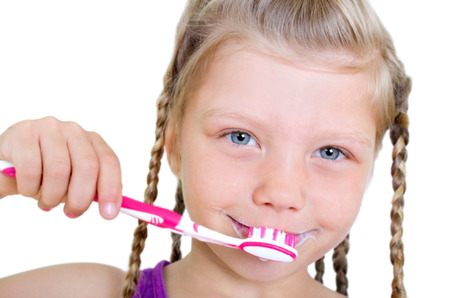 Little girl with long braids dressing up with pink teeth toothbrush against white background photo