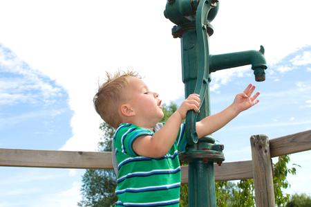 bomba de agua: muchacho sediento bombea a una bomba de agua para el agua