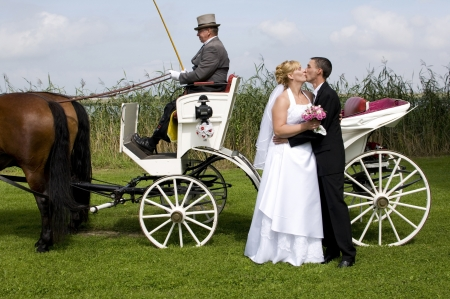 newlywed bridal couple in front of a white horse-drawn carriage