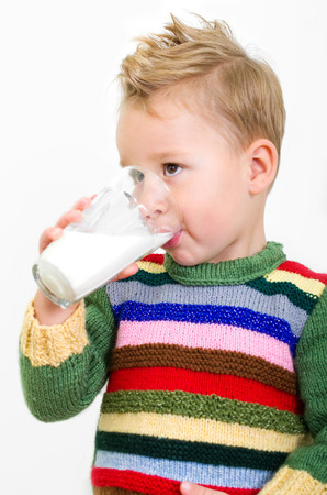 Little boy in knitted sweater drinking a big glass of milk against white background Reklamní fotografie