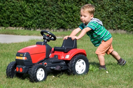 Little boy pushing toy tractor on a meadow