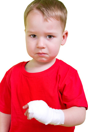 maltreatment: Little Boy in bandage around the arm looks sad in front of white background