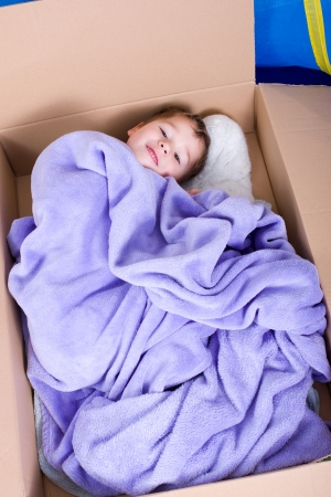 naptime: Little boy is lying in a cardboard box and revealed to be