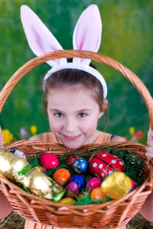 Laughing girl with Easter basket and bunny ears in front of a green background photo