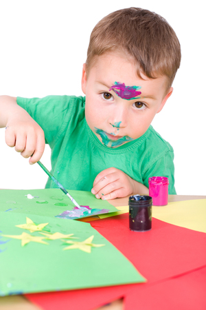 little boy paints with brushes photo