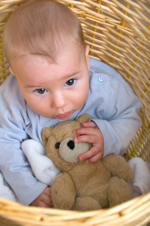 maltreatment: Little boy sitting in the laundry basket and looks anxiously to top