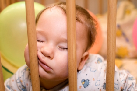 agotado: El bebé duerme con la cara divertida en el corral