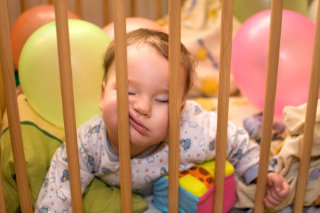 Baby sleeps in the playpen with his face between the bars