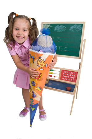 enrollment: Girl with funny hairstyle on the day of enrollment in front of a blackboard with a large sugar cone