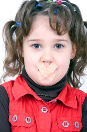 nonsense: little girl with funny hairstyle has a plaster on the mouth because to be quiet