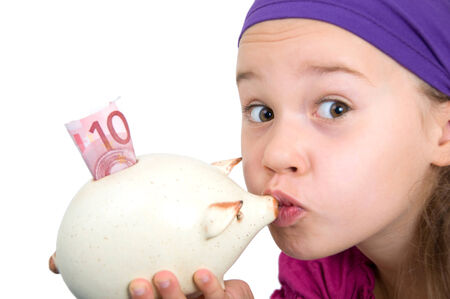 sparingly: Little girl kissing her piggy bank with 10 euros in it
