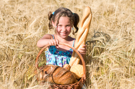 laughing Girl in the cornfield with bread basket photo