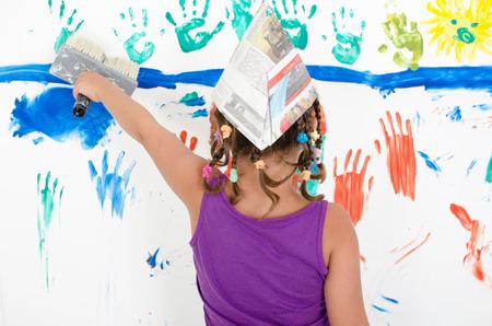 tinkered: ni�a con coletas y sombrero de papel vanamente pintando una pared