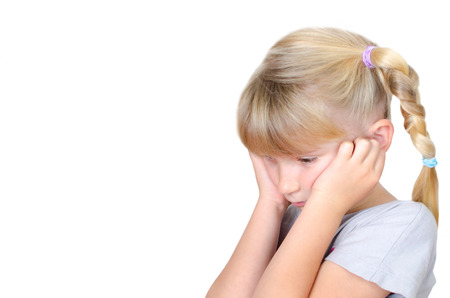 traumatized: Little girl holding her ears and looks sad Stock Photo