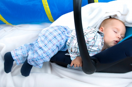 exhaustion: Baby sleeps in a baby carrier from exhaustion Stock Photo