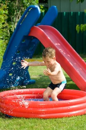 Little boy having fun in the paddling pool in the garden Banco de Imagens