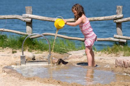 Meisje spelen op het water in een modderpoel