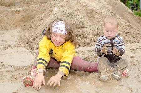 De kinderen zitten in een modderpoel en spelen