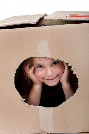 Glückliches Mädchen schaut durch ein Loch in den Karton Standard-Bild - 25272561