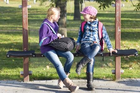 twee meisjes te wachten op de bus en praten met elkaar